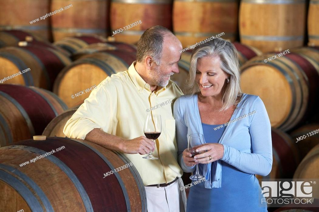 Stock Photo: Man and woman with wine-glass aside wine casks.