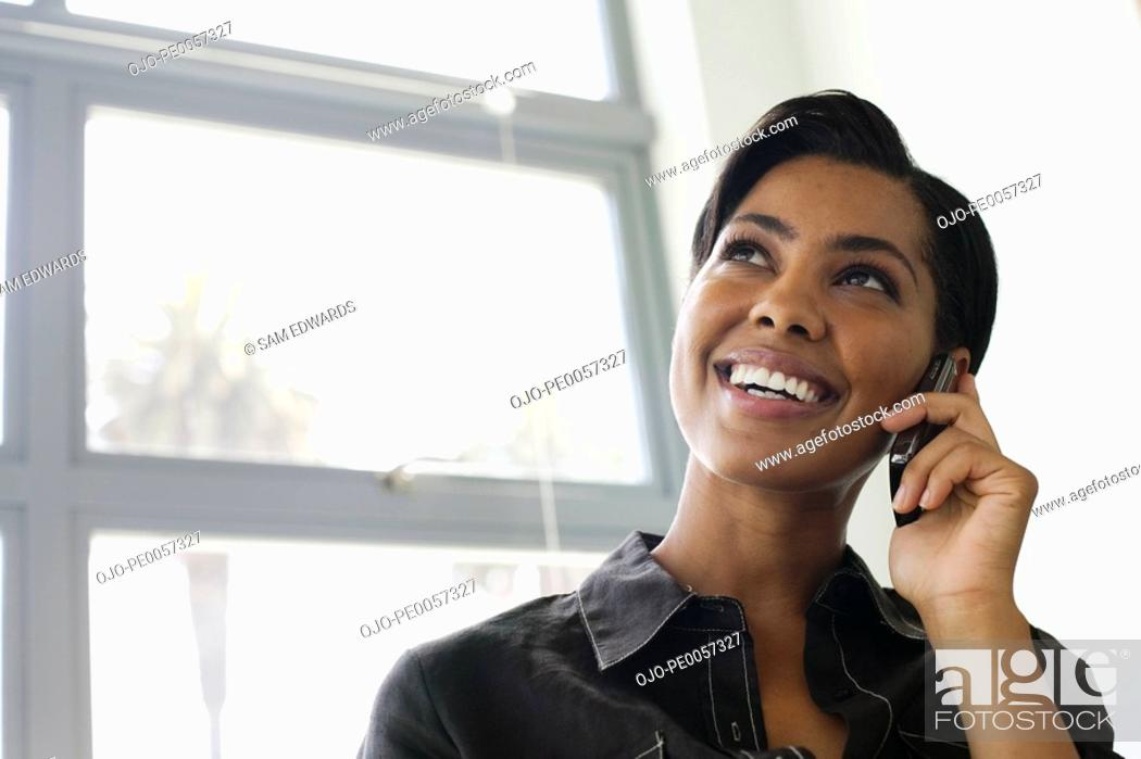 Stock Photo: Businesswoman on her mobile phone in office.