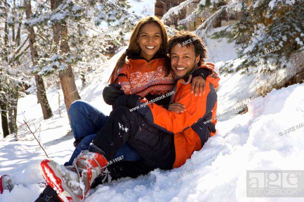 Stock Photo: Portrait of mixed race couple sitting in snow.