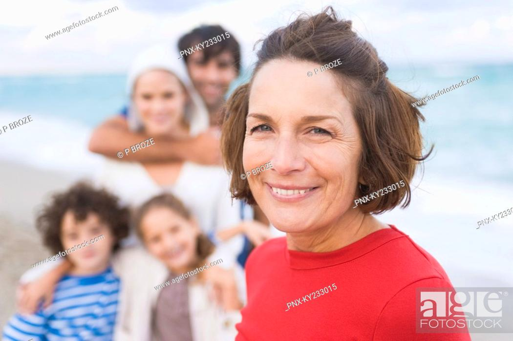 Stock Photo: Woman smiling with her family on the beach.