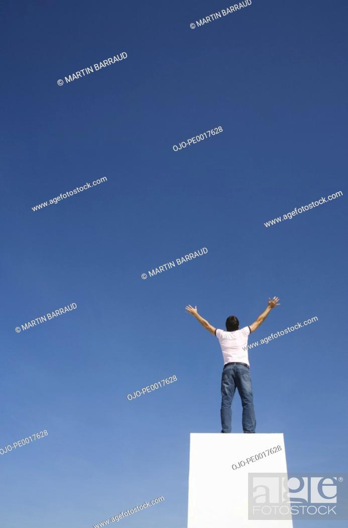 Stock Photo: Man standing on pedestal or wall with arms up and blue sky.