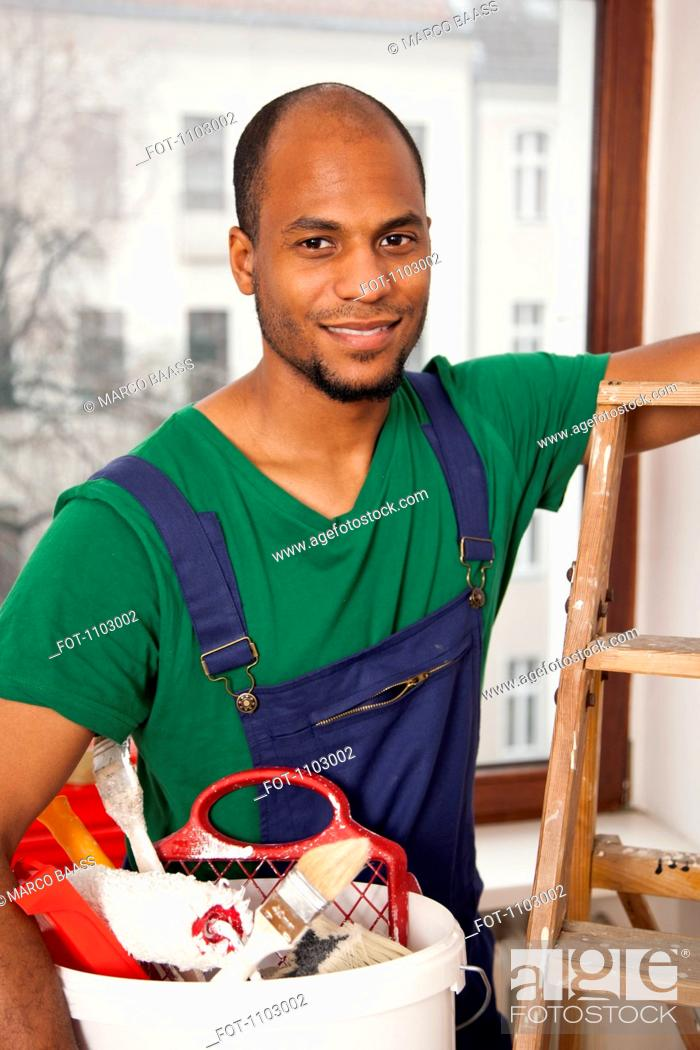Stock Photo: A man holding a bucket of paint supplies preparing to climb a ladder.