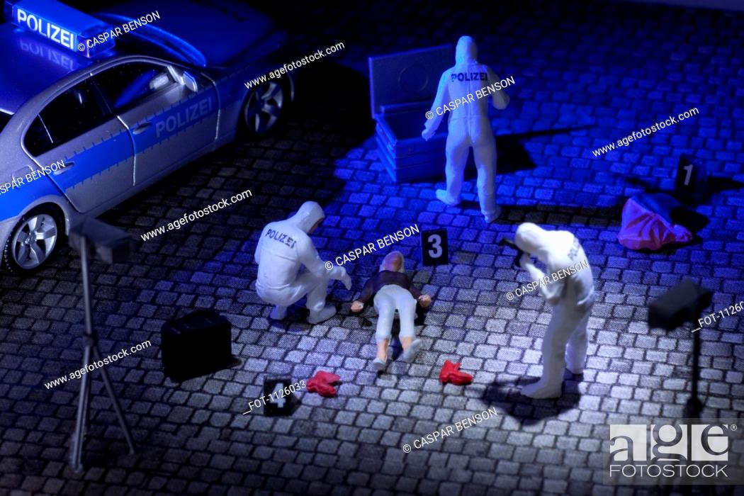 Stock Photo: A diorama of a miniature forensics team collecting evidence at a murder scene.