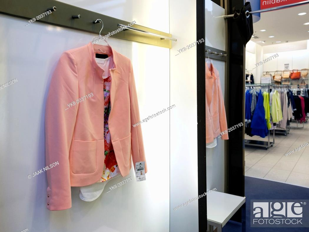 Stock Photo: Woman`s jacket hanging in dressing cabin, reflection, mirror. Retail store, shop, shopping.