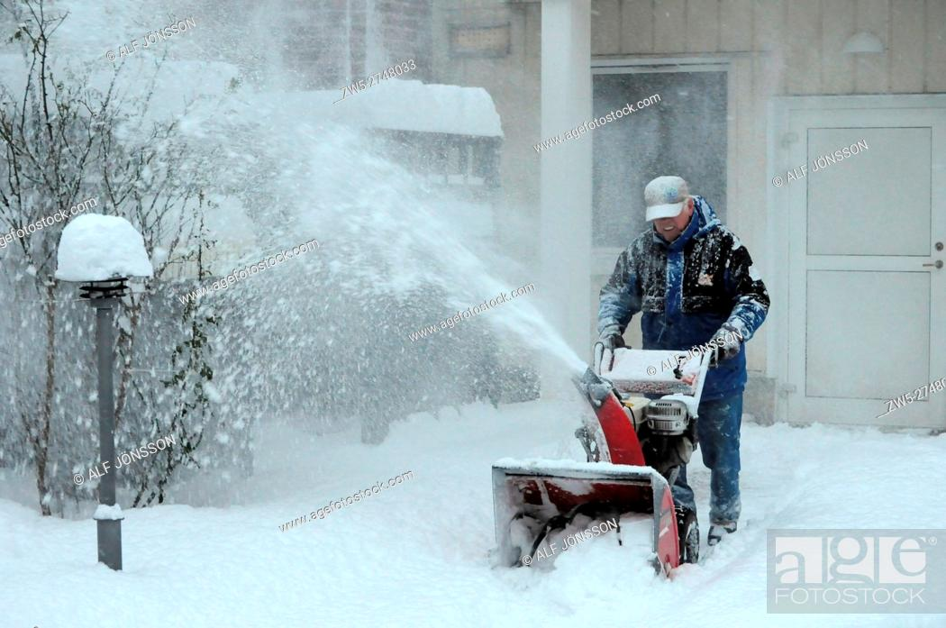 Photo de stock: Man with snowblower clearing snow.