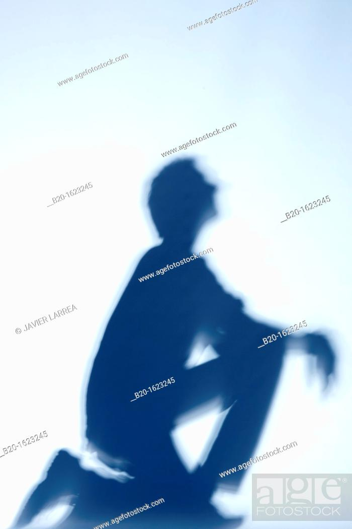 Stock Photo: Shadow, young boy crouched, looking ahead.