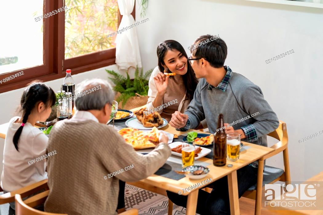Photo de stock: Happy asian multigenerational family of dad mom daughter girl and grandfather eating lunch together at home. Happy family engagement togetherness concept.
