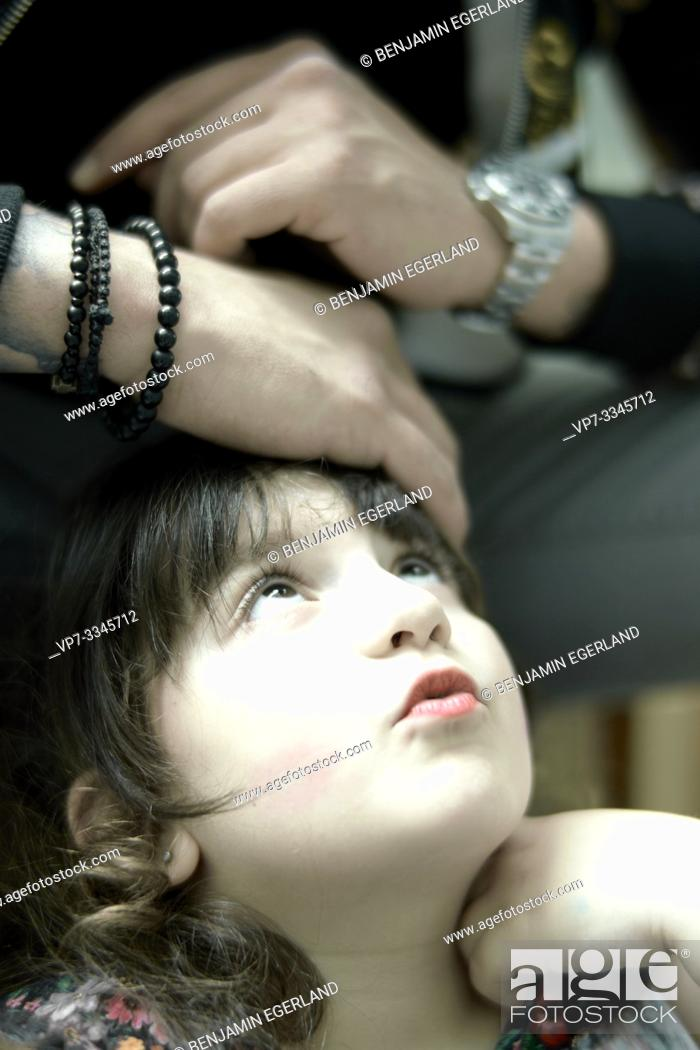 Imagen: daughter looking up at protective hands of father.