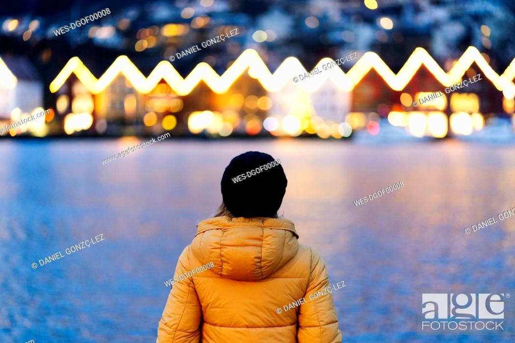 Stock Photo: Rear view of woman wearing a yellow jacket and standing at harbour in Bergen, Norway.