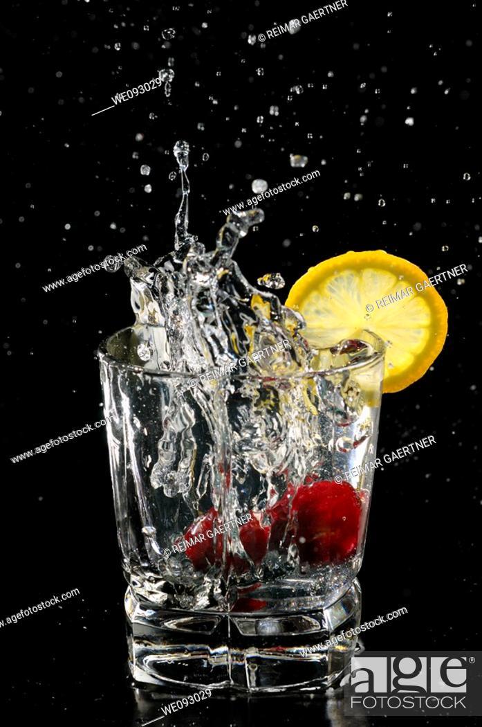 Stock Photo: Cherries splashing into sparkling water glass with lemon slice on black background.