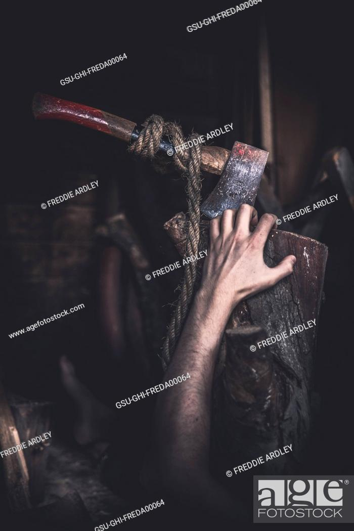 Stock Photo: Male Hand Reaching for Axe in Woodshed.