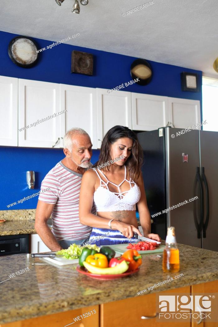 Stock Photo: Older man and young woman enjoying cutting vegetables in their kitchen.