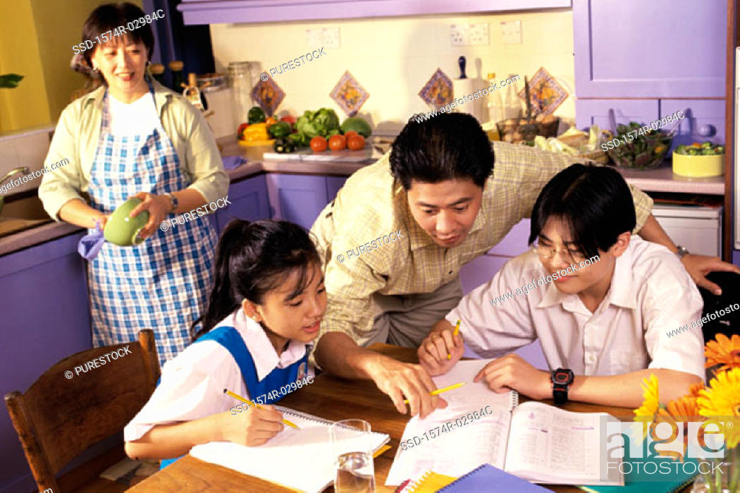 Stock Photo: Father helping his son and daughter with their homework.