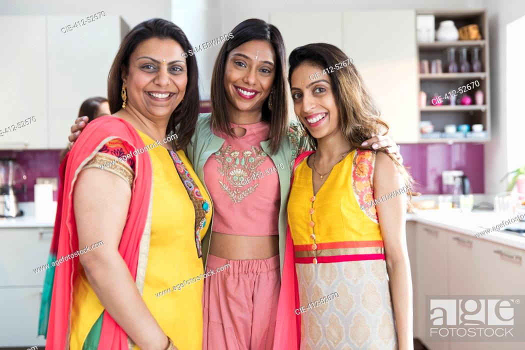 Stock Photo: Portrait happy Indian sisters in saris in kitchen.