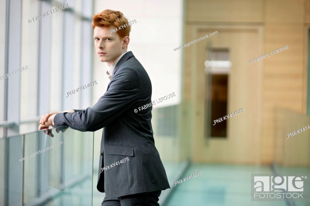 Stock Photo: Portrait of a businessman staring in a corridor.