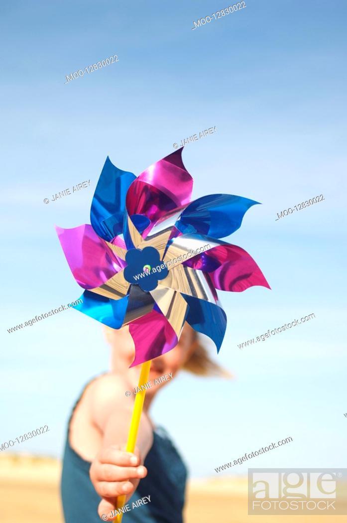 Stock Photo: Girl standing on beach holding pinwheel close up of pinwheel.