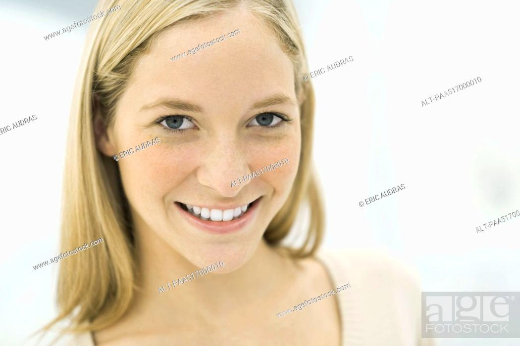 Stock Photo: Young woman smiling at camera, portrait.
