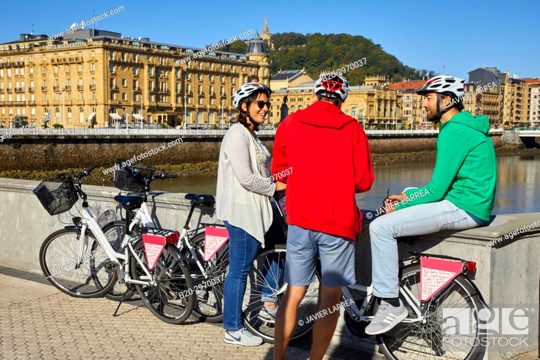 Photo de stock: Group of tourists and guide making a bicycle tour through the city, Maria Cristina Hotel, Victoria Eugenia Theatre, Urumea river, Donostia, San Sebastian.