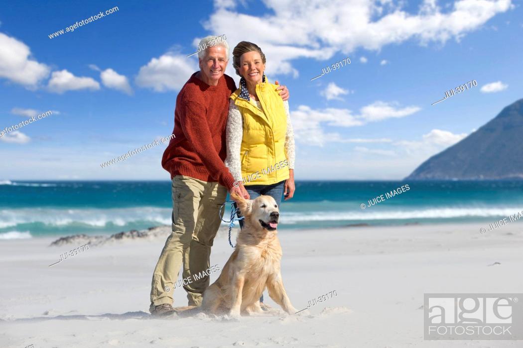 Stock Photo: Portrait of smiling senior couple with dog on sunny beach.