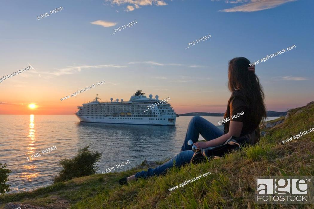 Stock Photo: Young woman is watching a big ship during a sunset time, Rovinj in Croatia.