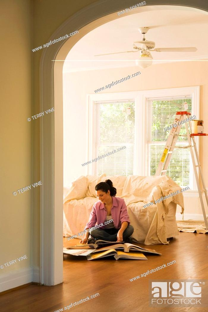 Stock Photo: Hispanic woman looking at textile swatches in new home.