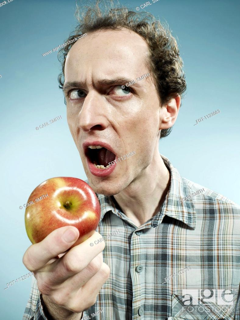 Stock Photo: A frowning man preparing to bite into an apple.