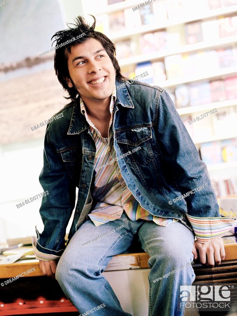 Stock Photo: Hispanic man sitting on music store counter.