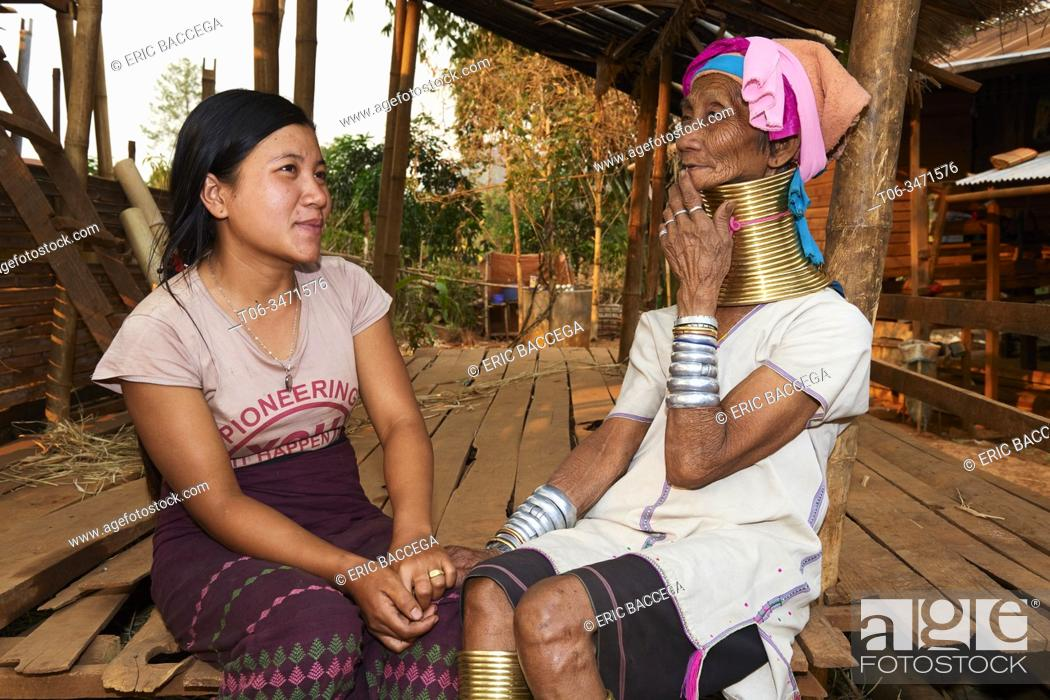 Stock Photo: Generation gap. Kayan Lahwi woman with brass neck coils and traditional clothing chatting with her grand daughter, who is not wearing any coils and dressed in a.