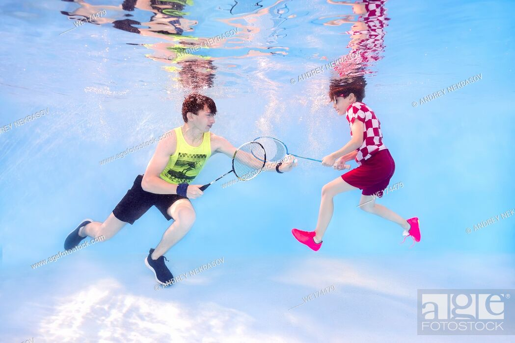 Stock Photo: Two teenagers playing badminton underwater.
