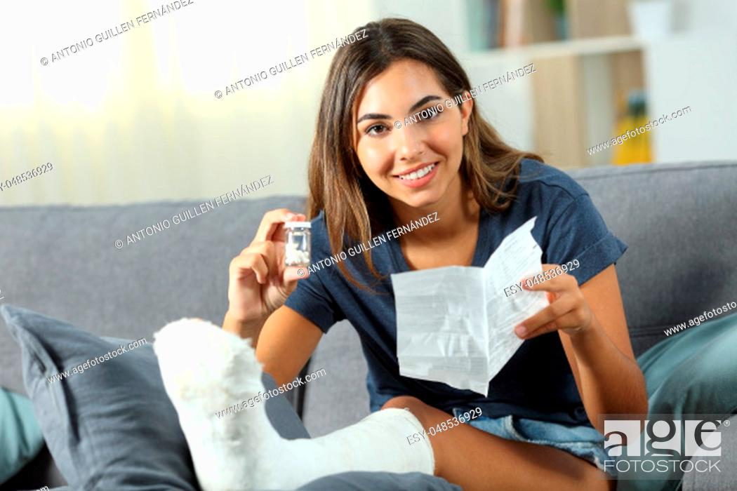 Stock Photo: Happy disabled woman showing a bottle of pills sitting on a couch in the living room at home.