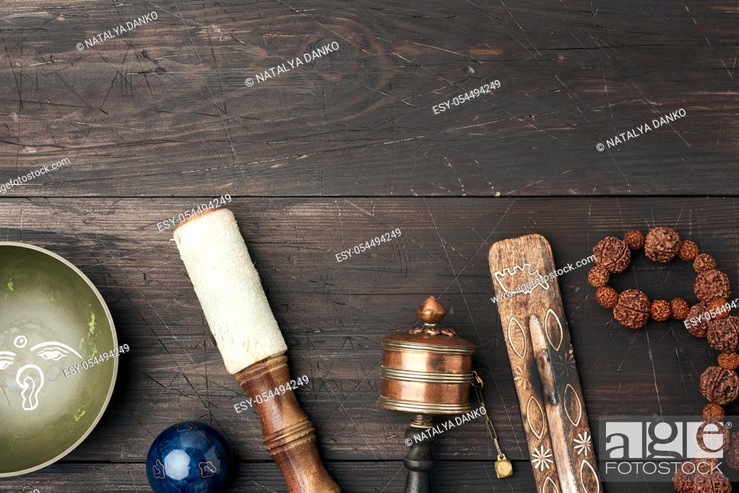 Stock Photo: Copper singing bowl, prayer beads, prayer drum and other Tibetan religious objects for meditation and alternative medicine on a brown wooden background.