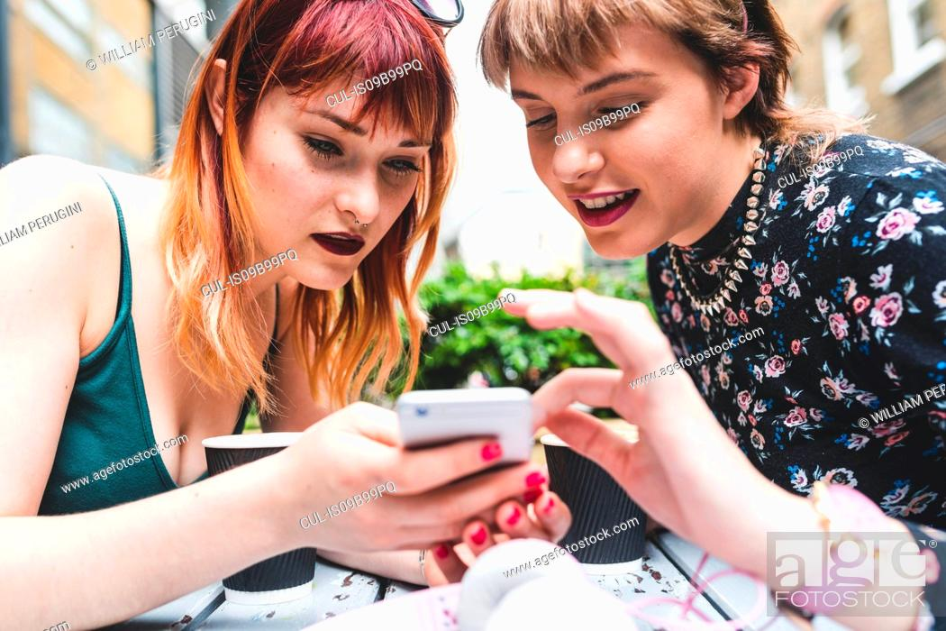 Imagen: Two young women at sidewalk cafe table looking at smartphone.