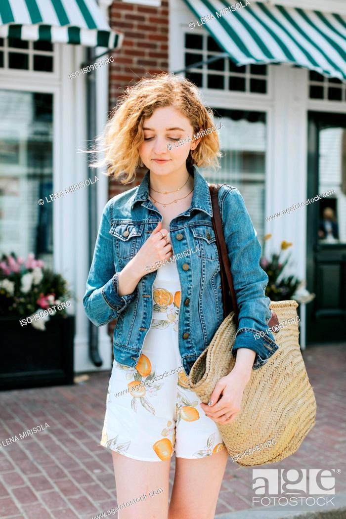 Stock Photo: Young woman on street carrying straw bag, Menemsha, Martha's Vineyard, Massachusetts, USA.