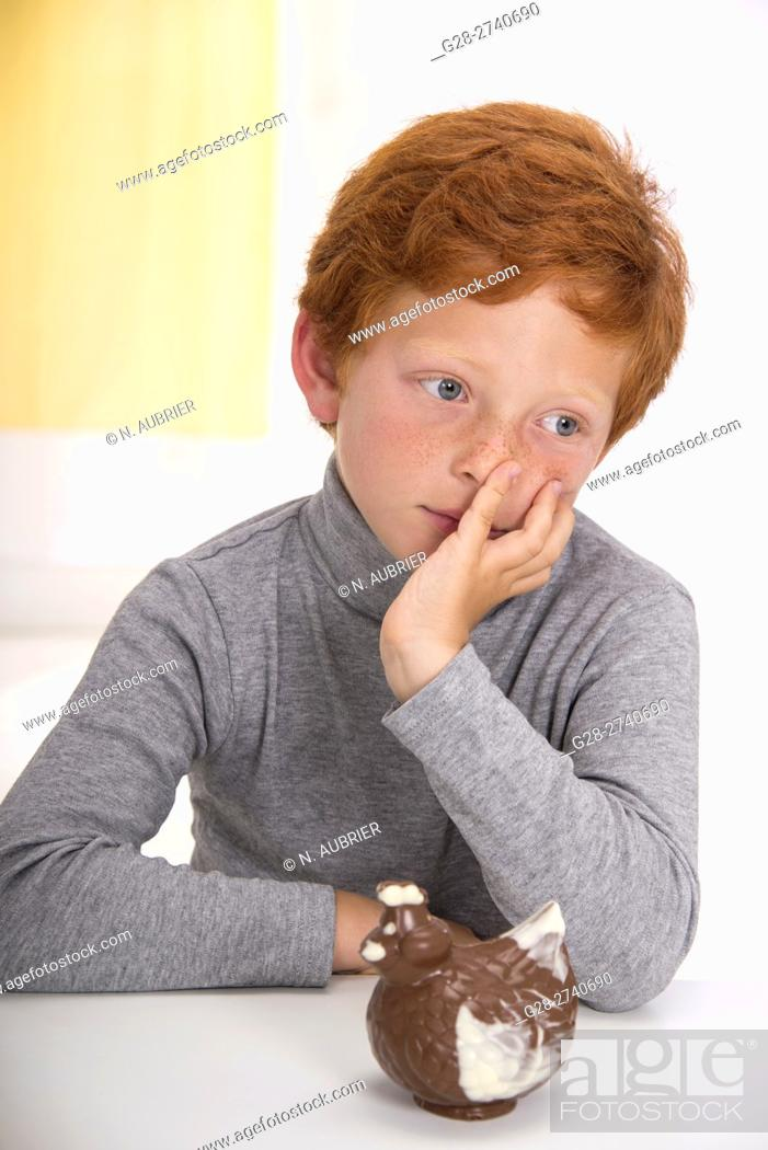 Stock Photo: Little boy with red hair, head resting in one hand, thoughtful in front of an easter chocolate hen.