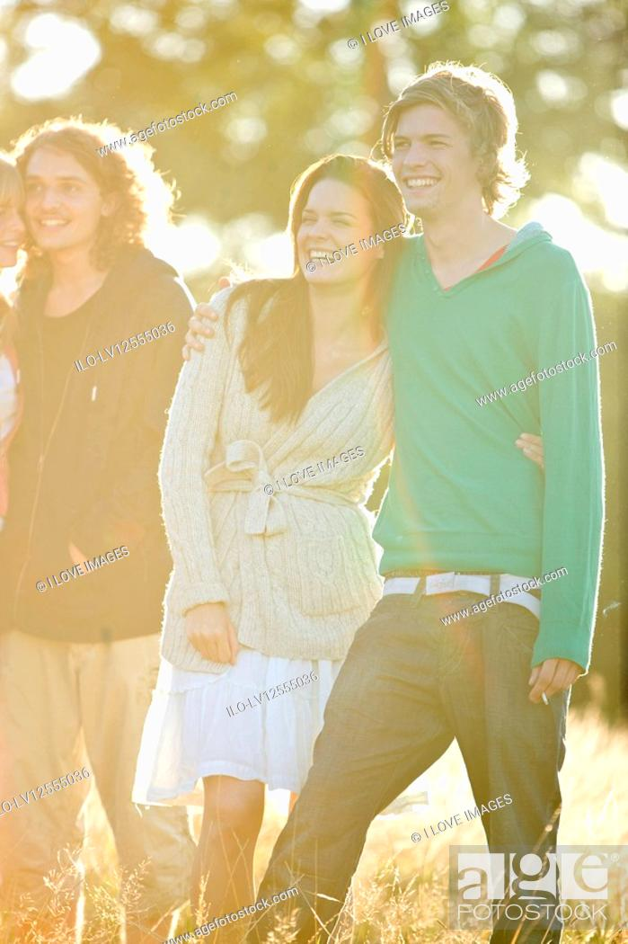 Stock Photo: Two young couples standing in a field, smiling.