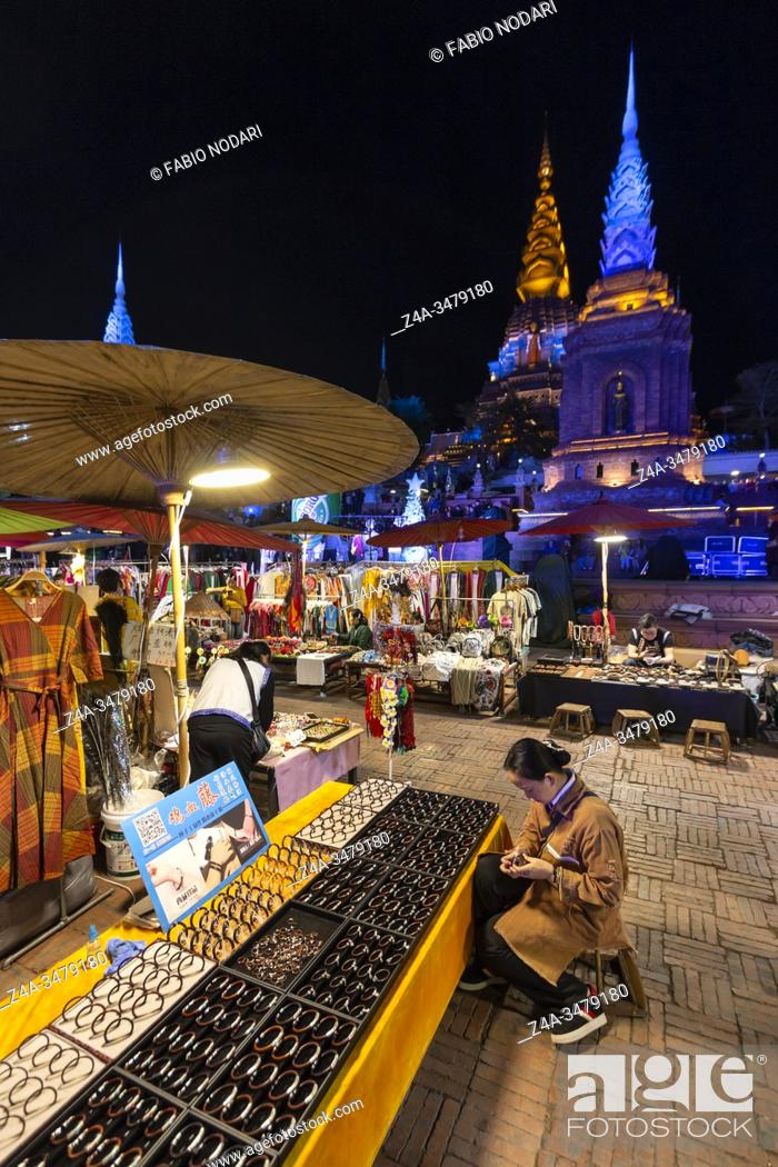 Stock Photo: Jinghong, China - December 30, 2019: Gaozhuang Night Market at night with tourist walking by.