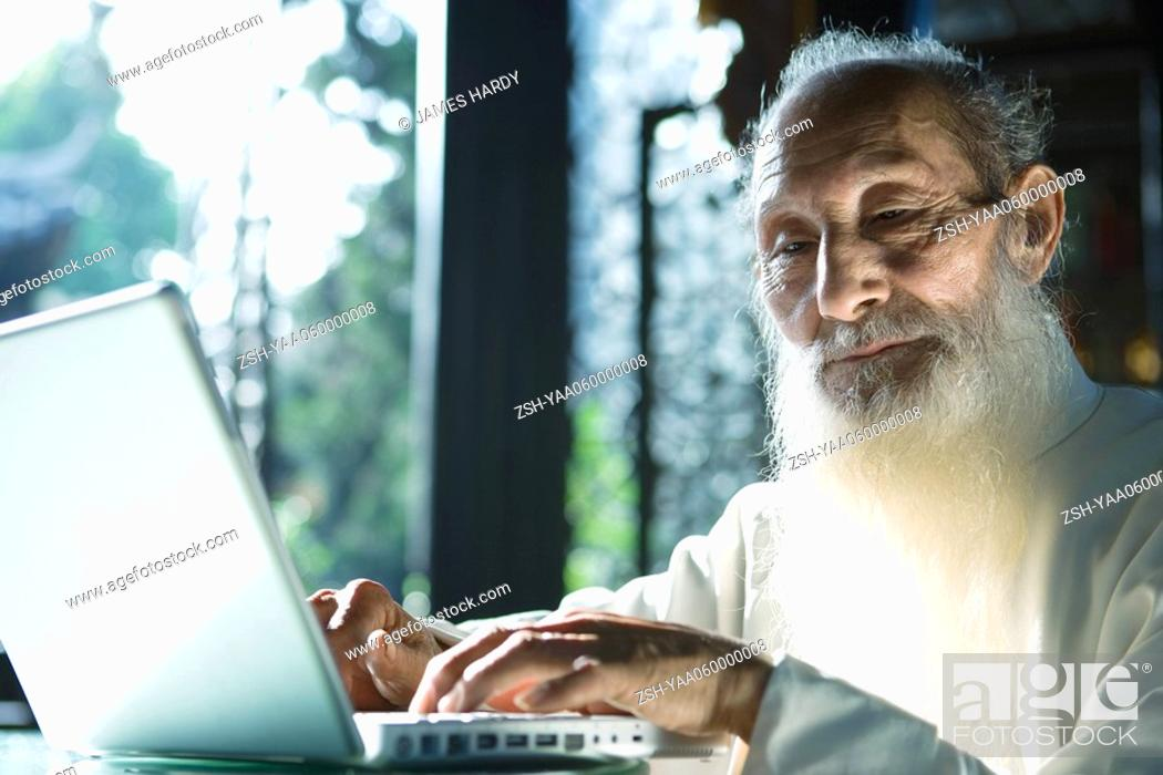 Stock Photo: Elderly man in traditional Chinese clothing using laptop computer.