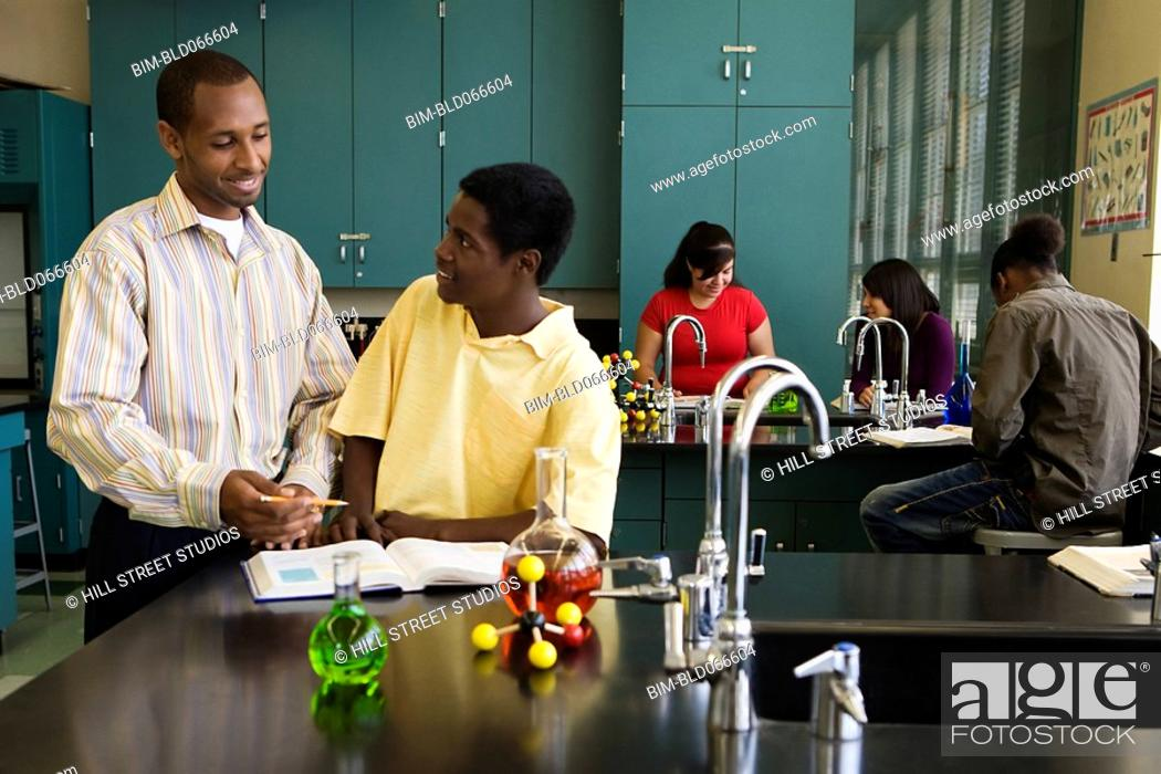 Stock Photo: African teacher helping student in chemistry lab.