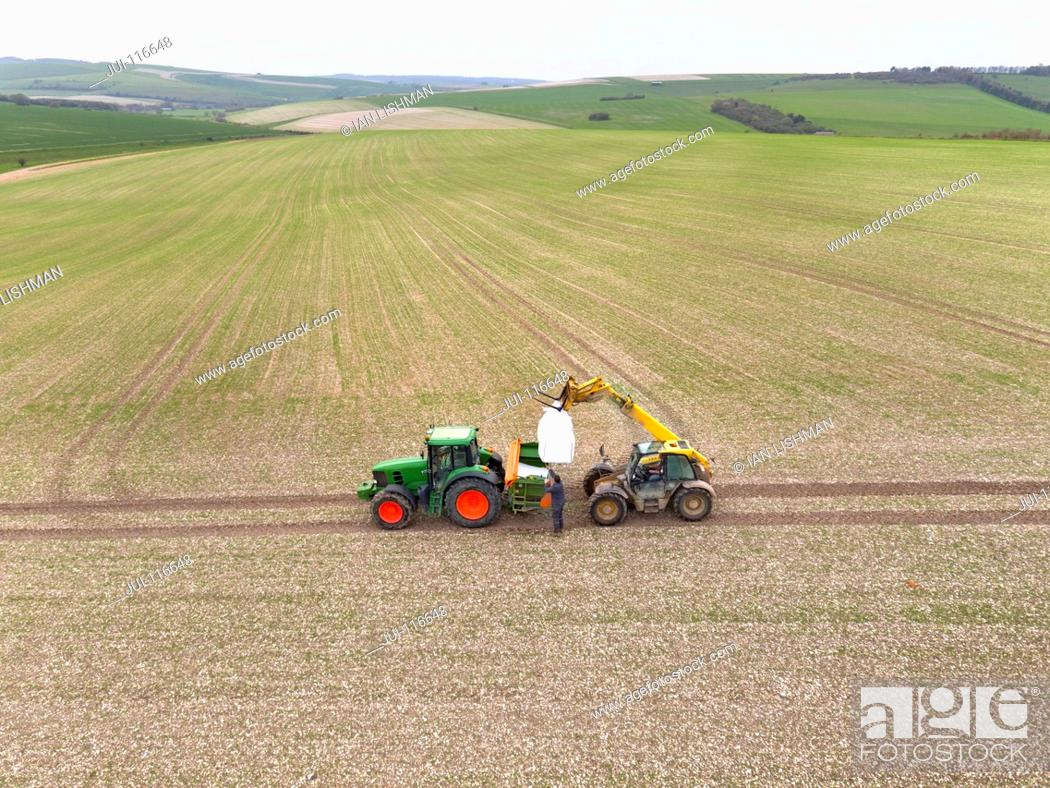 Stock Photo: Aerial View Of Loading Fertilizer Into Spreader On Tractor.