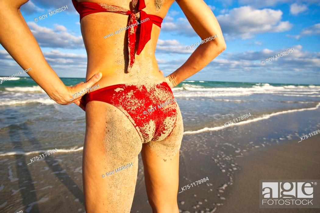 Stock Photo: Woman with sand on her behind standing on the beach.