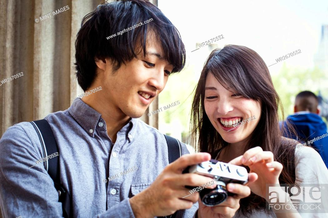 Stock Photo: Young Japanese man and woman enjoying a day out in London, holding at a digital camera, smiling.