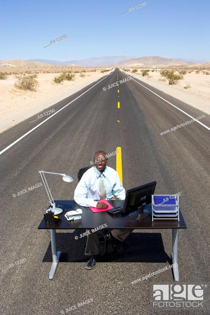 Stock Photo: Businessman at desk in middle of road in desert, smiling, portrait, elevated view.