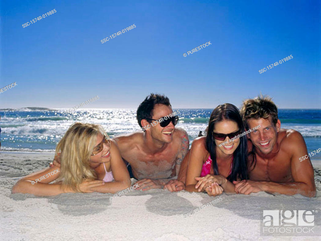 Stock Photo: Two young couples lying on the beach.