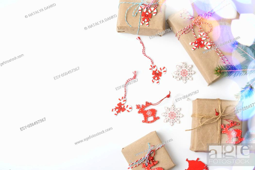 Stock Photo: gift boxes wrapped in brown paper and tied with a golden ribbon on a white background with bokeh, top view, copy space.