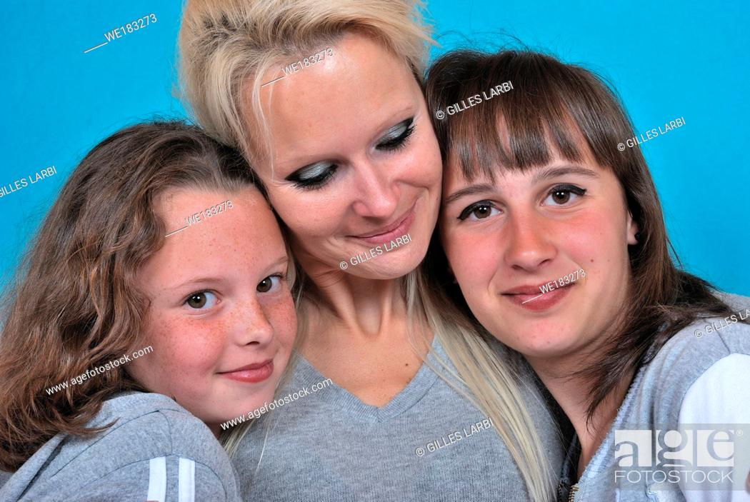 Stock Photo: A mother smiles as she receives a kiss on the cheek from her young daughters.
