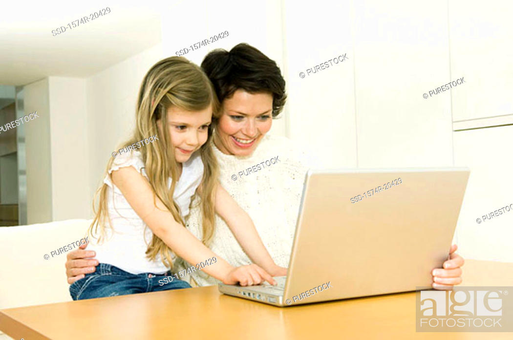 Stock Photo: Close-up of a girl using a laptop with her mother.