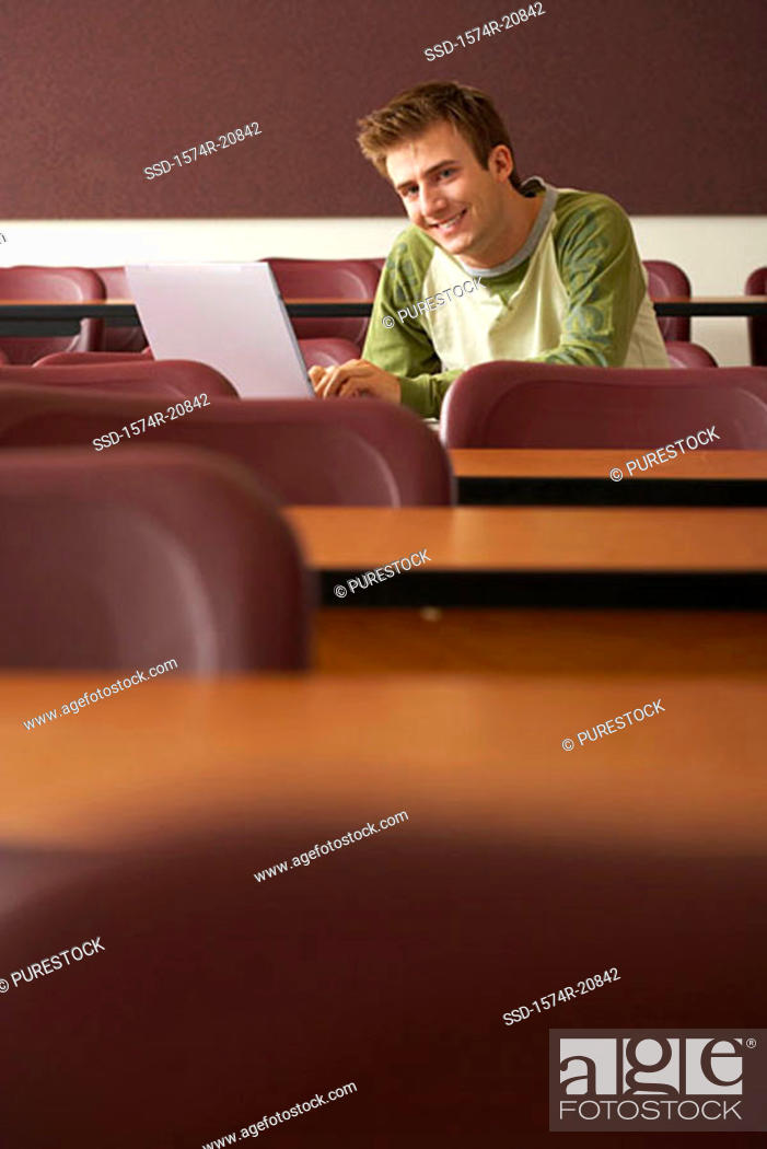 Stock Photo: Portrait of a college student sitting in a lecture hall and using a laptop.