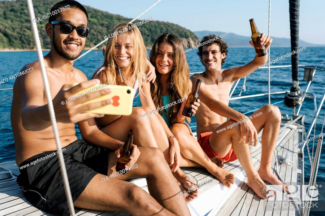 Imagen: Friends taking selfie on sailboat, Italy.