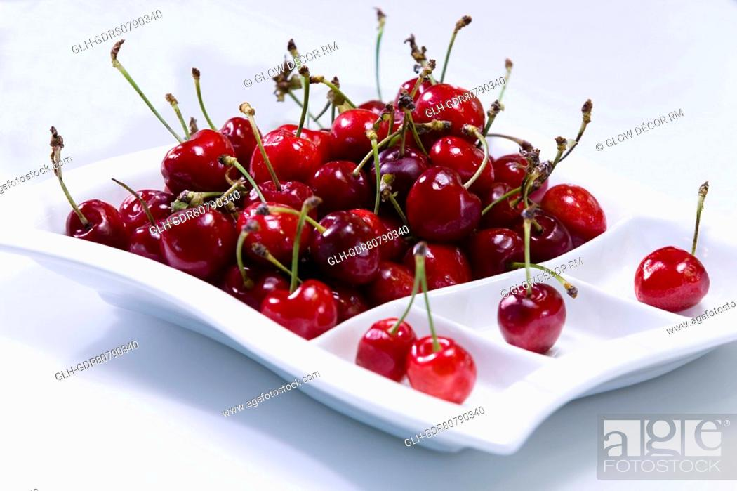 Photo de stock: Cherries in a tray on a table.