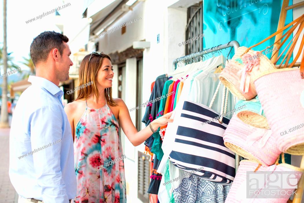 Stock Photo: Couple shopping for beach bag at shop front, Majorca, Spain.